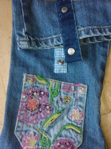Popper fasteners and pocket detail on denim bag
