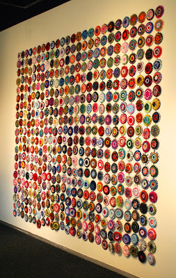 Woven CD looms displayed on wall hanging