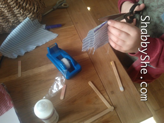 making sails for milk bottle boats using lolly sticks and scrap fabric
